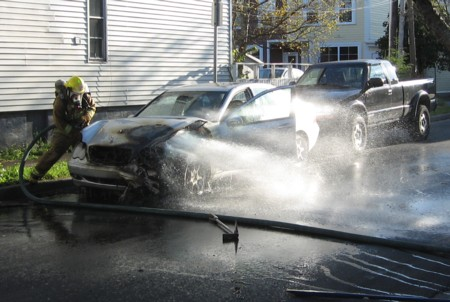 Firefighters squeezed a hose under the hood to put the fire out.