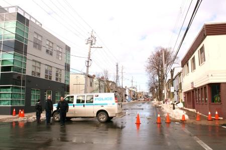 Police send cars down West Street  just before noon on Saturday after a water main break damaged asphalt on Agricola.